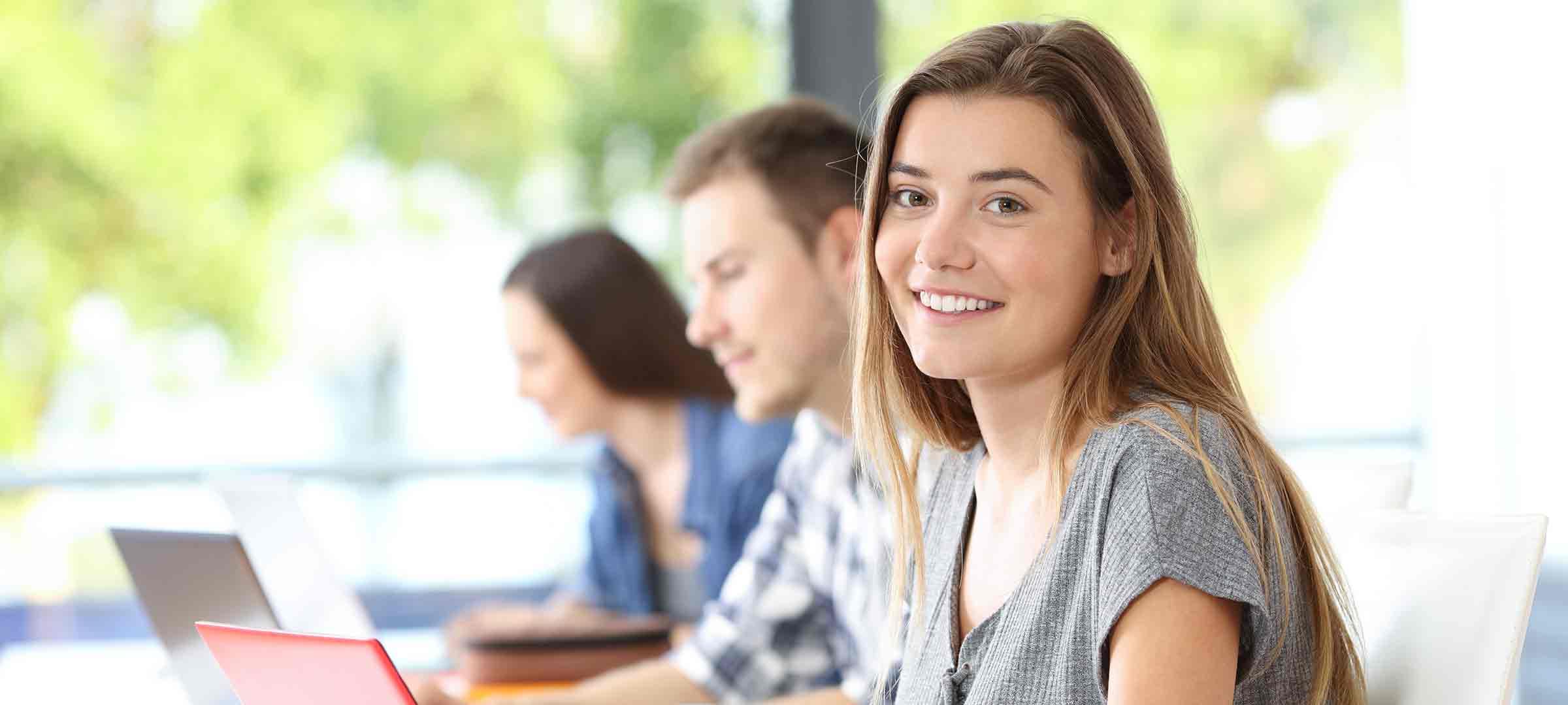 Titelbild: Studentin sitzt mit Kommilitonen im Hörsaal