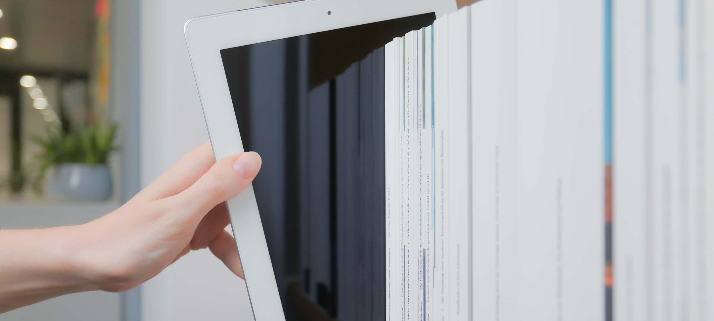 Titelbild: Tablet in einem Regal mit Büchern