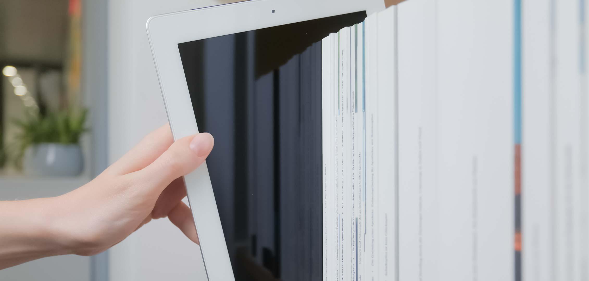 Vorschaubild: Tablet in einem Regal mit Büchern