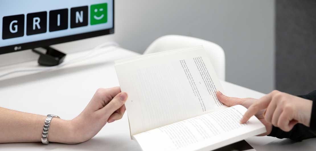 Vorschaubild: Zwei Personen arbeiten mit einem Buch
