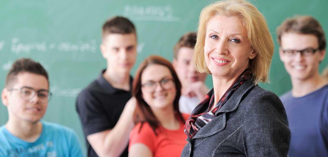 Vorschaubild: Lehrerin steht im Klassenraum vor ihrer Klasse