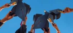 Bild von Händen, die Absolventenkappen nach oben halten