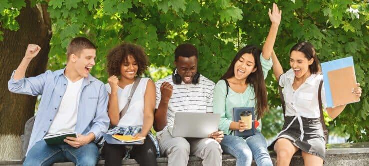 Bild von Studierenden, die auf einen Laptop sehen und jubeln